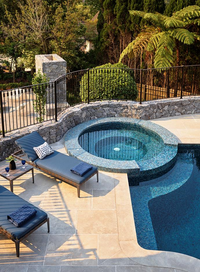 The garden extends to provide a scenic backdrop to the pool. 'Mustique' aluminium chaise longue in Sunbrella canvas in Indigo and 'Mustique' teak side table from Restoration Hardware. Custom cushions in Gaston y Daniela fabric from Domestic Textile.