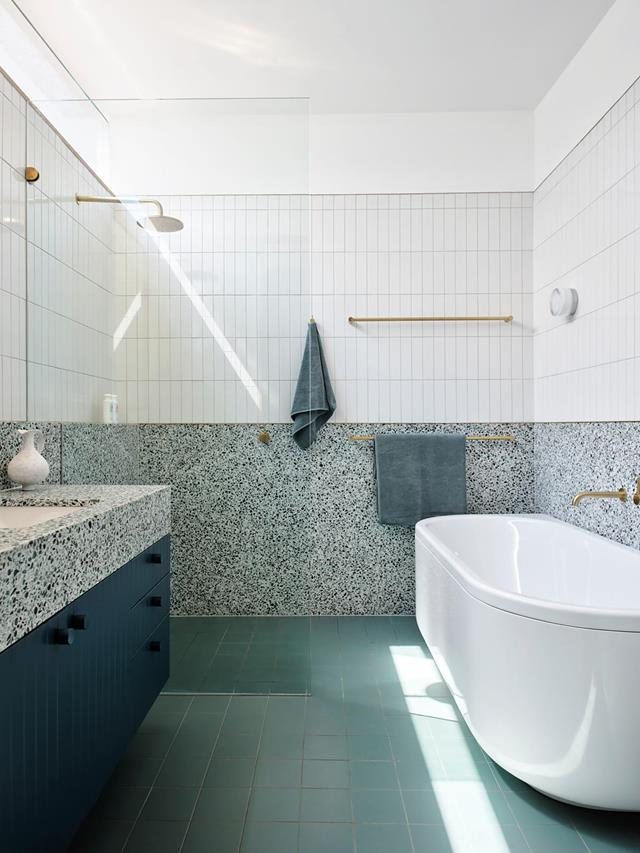 """This bathroom, [designed by Arent&Pyke](https://www.homestolove.com.au/relaxed-harbourside-home-with-australian-palette-21994 target=""""_blank""""), echos the shades of eucalypts in soft greens and the deep blues of the ocean. The excitement of the terrazzo slab walls is taken up to a datum line with a fine brass detail providing a subtle break between the tiles above."""
