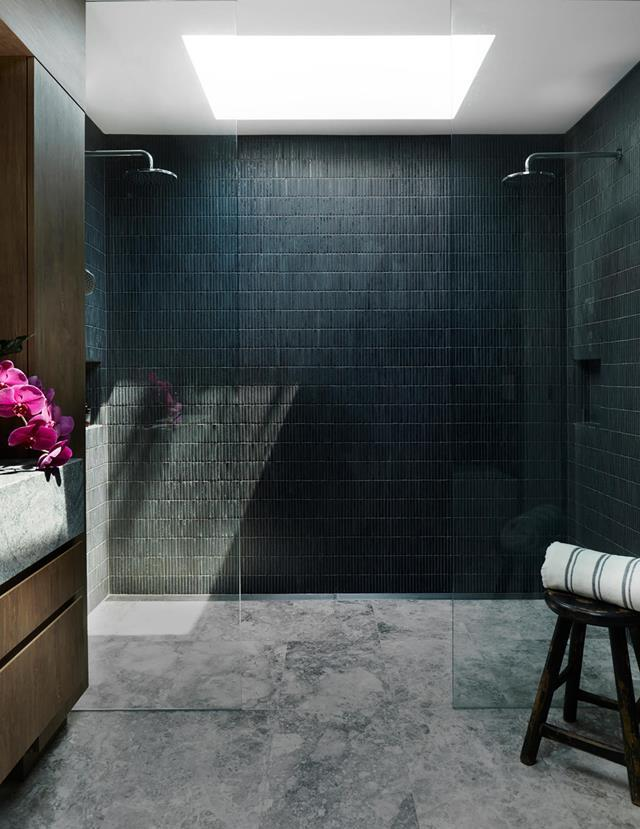 """Finger tiles in a deep blue tone create a striking feature wall in the double walk-in shower of this [contemporary bathroom](https://www.homestolove.com.au/preview/walk-in-showers-21163 target=""""_blank""""). A well positioned skylight allows light to flood the space while timber joinery provides additional warmth."""