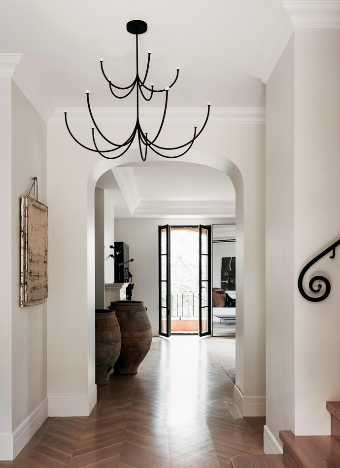 A calming ambience pervades the entrance, with its neutral tones and hero pieces. Matter Made 'Arca' two-tier chandelier by Philippe Malouin from Criteria. Vintage urns from Sally Beresford. Artwork by Jupp Linssen. The parquetry flooring was original, sanded and refinished in a natural shade.