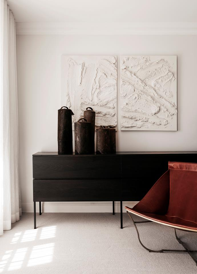 Opposite page, from top Also in the master bedroom, a custom cabinet by Les Interieurs sits beneath a textured plaster artwork by Sam Whiteman. Vintage camel bells from Les Interieurs. Baxter leather chair from Cavit & Co. Bremworth 'Tussore' carpet in Sumac.