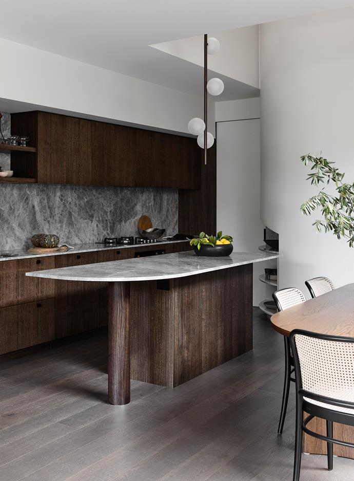 Vertically quarter-cut timber-veneer joinery creates a dark backdrop in this kitchen conceived by architect Maria Danos to provide a dramatic 'aerial perspective'.  Tapware in a muted gunmetal finish is matched tonally to the palette, and dark handles punctuate the joinery faces. The curvilinear island bench enables comfortable access around the bench for perching while still allowing a good spatial flow.