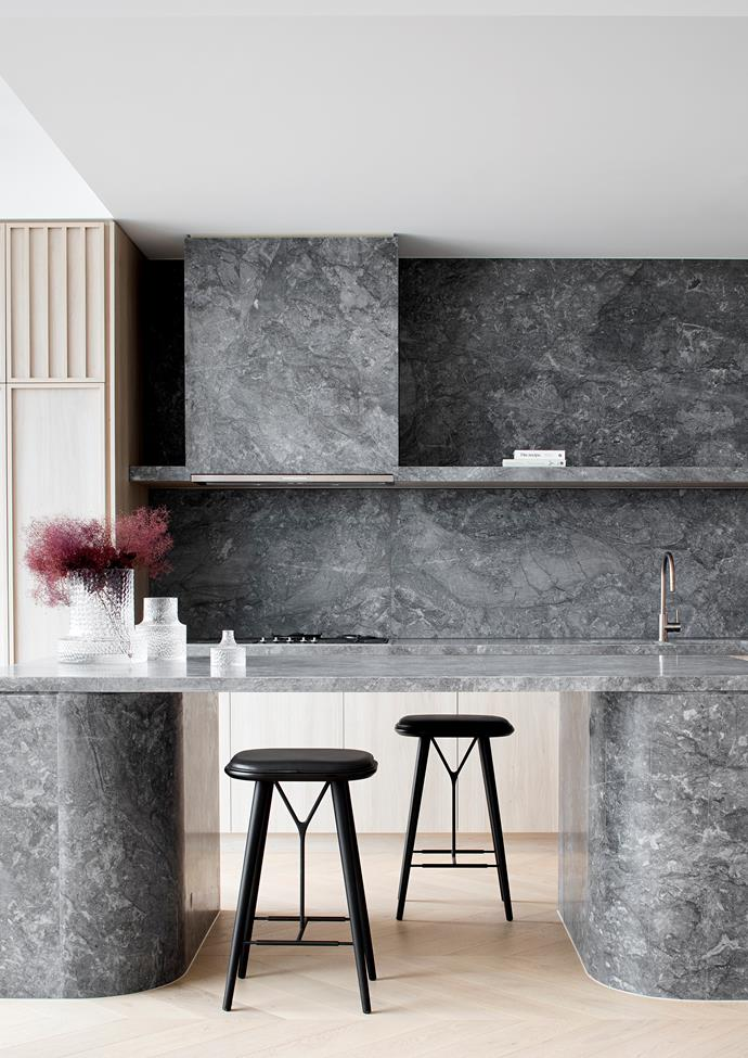"""There's a monolithic quality to the island bench that architect Ben Robertson, director of Tecture, designed for this penthouse apartment. """"I chose Era Silver stone for its depth and moodiness,"""" he says. """"It was all about selecting a stone that could convey a sense of grandeur and sophistication, but also stand up to being used at this sort of scale."""" Soft-toned oak-veneer cabinetry and pale-timber chevron flooring work to counter the weight of the stone."""