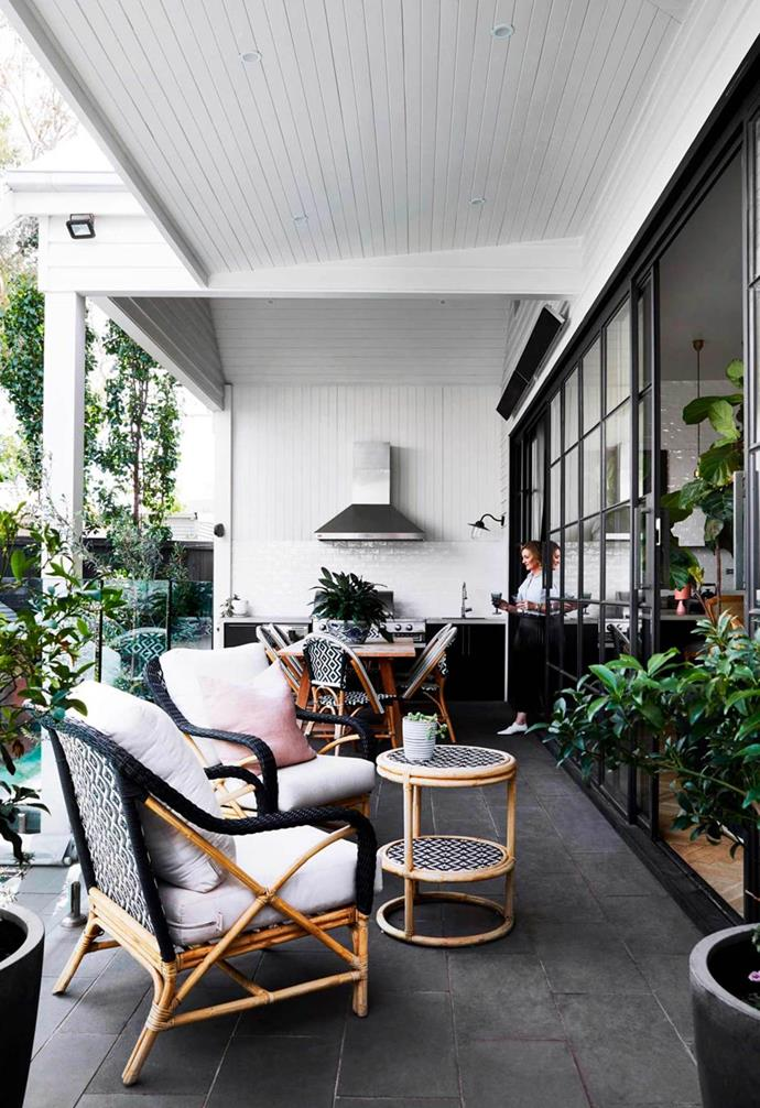 "This [weatherboard home](https://www.homestolove.com.au/renovated-white-weatherboard-home-melbourne-21530|target=""_blank"") received an all-white revamp, giving it a fresh new look. Connecting seamlessly with the indoors courtesy of sliding steel-framed doors, the outdoor kitchen space features black cabinetry and a sleek stainless steel rangehood to finish the look."