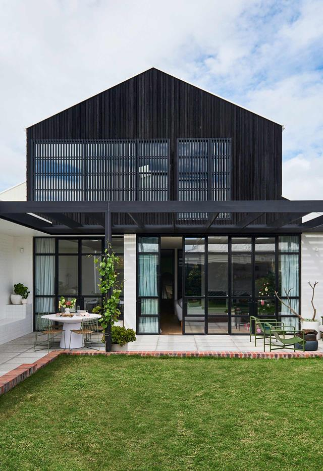 "The black timber cladding of this [Edwardian-style home's](https://www.homestolove.com.au/edwardian-style-house-geelong-21986|target=""_blank"")  modern extension is perfectly complemented by a series of steel-framed doors."