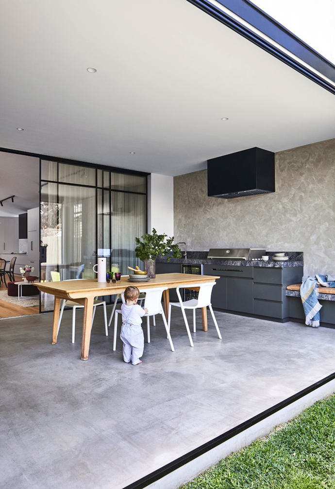 Angus ventures outside to explore the outdoor room that's used for entertaining.  An extendable Ethnicraft oak 'Bok' dining table paired with 'Kazbah' chairs from Relax House create the perfect spot to relax and the Emperador Grey marble-topped outdoor kitchen, designed and built by The Melbourne Joiner, makes cooking a breeze.