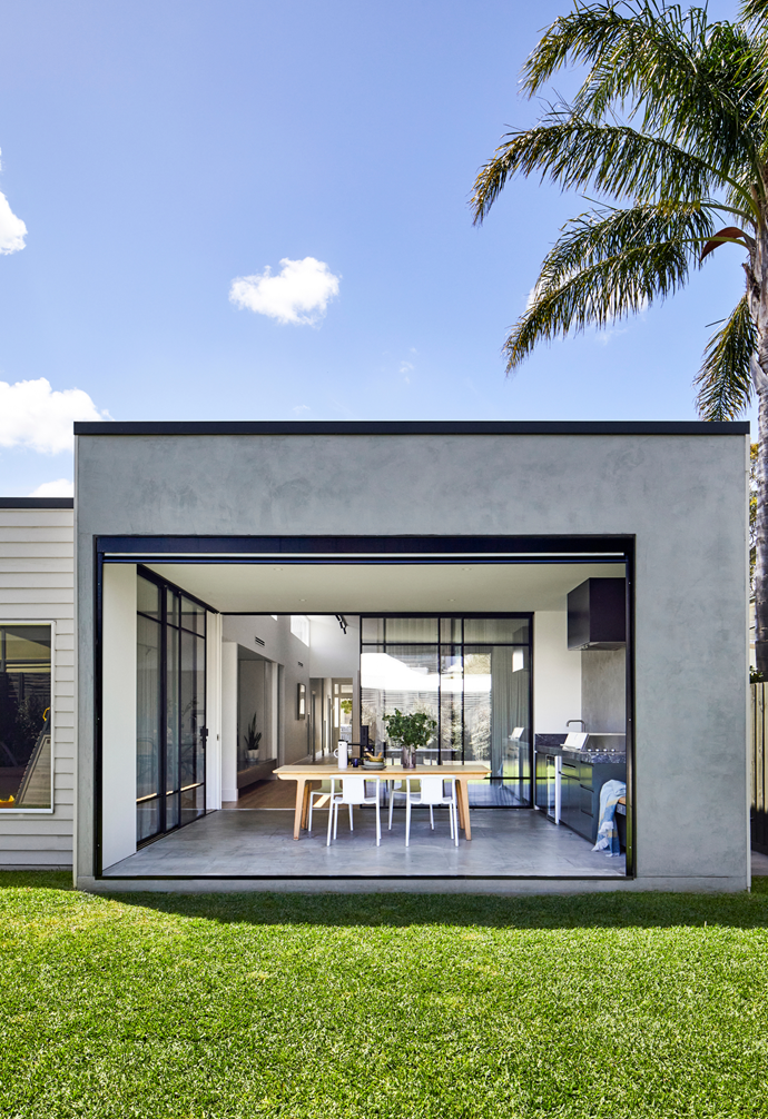 """From family barbecues to balmy dinner parties, Gemma and Dale have outdoor entertaining sorted with this outdoor room framed on both sides by fully retractable glazed doors. """"There's nothing better on a nice evening than opening up the sliding doors and sitting out here while the kids are playing outside,"""" says Gemma."""