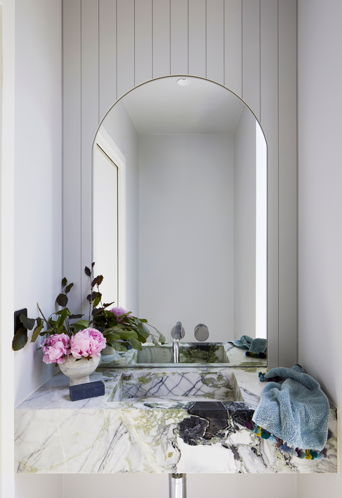 """The Ice Green marble from Signorino also reigns supreme in the home's luxurious powder room. """"The fully-integrated marble washbasin has to be my favourite feature here,"""" says Gemma. Tapware from Reece complements the modern look while the timber wall arch by The Melbourne Joiner is a shapely feature in the pared back room."""