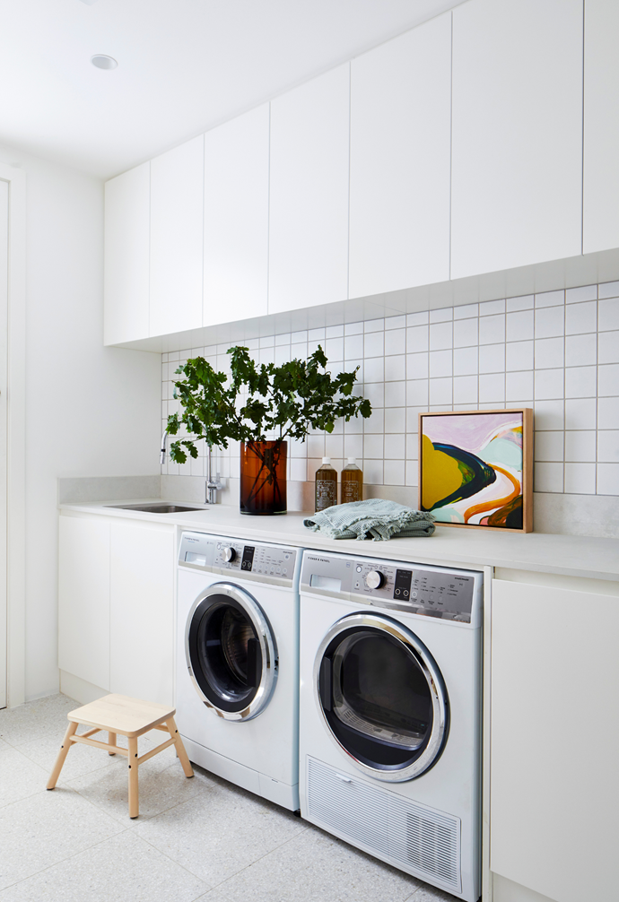 There's nothing at all utilitarian looking about this home's laundry, which proves that practicality can indeed be beautiful. A sea of 2-pac cabinetry, in half-strength Natural White by Dulux, has been created by The Melbourne Joiner for easy above-head storage while on-trend white mosaic wall tiles and terrazzo flooring – both from Signorino – add texture to the deliberately pared-back palette. Greenery in a vase and a beautiful original landscape by Jen Sievers Art - represented by Greenhouse Interiors - add shots of colour.