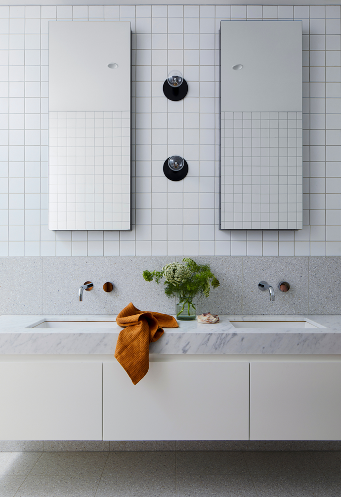 """""""It's such a luxury,"""" says Gemma of the added heating. White mosaic wall tiles from Signorino provide the chic match to the Carrara marble vanity, while Dowel Jones 'Lord Sconce' wall lights offer the right amount of task lighting when needed."""