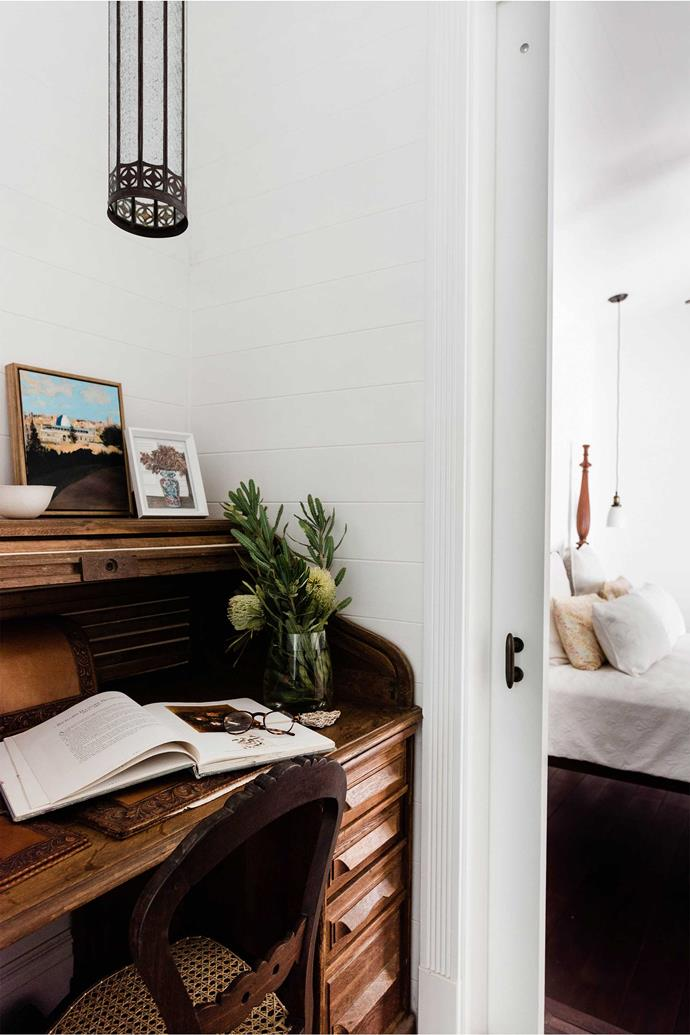 """**Vintage charm** <br> An antique roll-top desk decorated with flowers and paintings contrasts with crisp white walls, and is perfectly in keeping with the """"south-east Asia meets coastal house"""" feel of Vicki and Tony Lemarseny's [Peregian Beach home](https://www.homestolove.com.au/peregian-beach-house-22286
