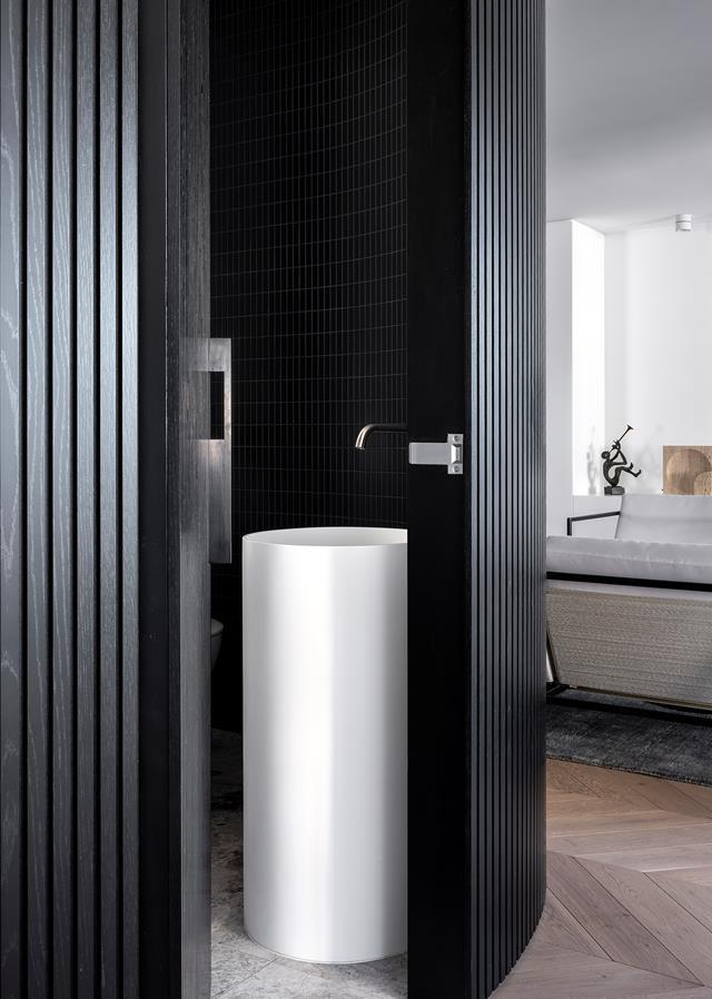 """A 'Brave' move in installing a curving wall in black devised by architect Brad Swartz delivers a cocooning mood within this newly opened up [one-bedroom apartment](https://www.homestolove.com.au/black-and-white-apartment-sydney-1-22289