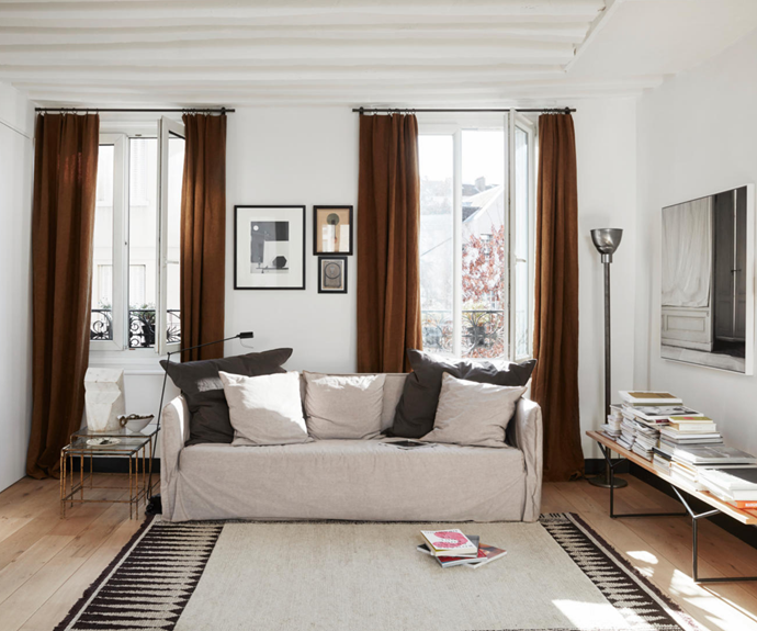 """Textiles from Rue Herold bring sophistication to the [living space](https://www.homestolove.com.au/living-room-essentials-3466 target=""""_blank""""), from the flax curtains to the sofa cover. Above are artworks by Vladimir Lebedev and Gilbert Garcin. A good yarn Balls of rope and thread bring instant warmth and texture to open wall shelves. These items illustrate Charlotte's intuitive and unexpected approach to decorating. Of her process she says, """"I find things along the way that I fall in love with and want to include in my home."""""""