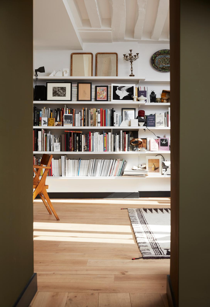 As Charlotte steps inside her home, she's welcomed by this view of a bookcase brimming with magazines, tomes, art and personal treasures.