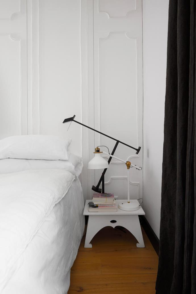 White stonewashed linen and cotton bedding in pillowy textures sets the tone in the bedroom. On the bedside table, which is from a flea market, are lamps from Artemide. The beautiful wallpaper behind the bed is by Farfelus Farfadets. It was designed to recreate the look of panelled walls. A