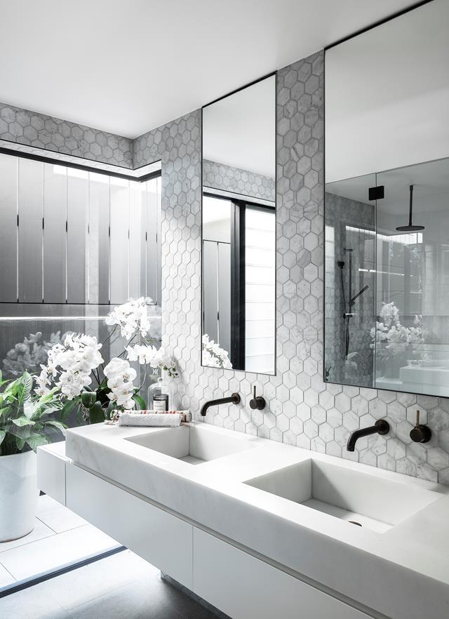 """Carrara marble hexagon tiles line the walls of this beautifully modern bathroom within a [striking coastal home](https://www.homestolove.com.au/california-bungalow-transformed-into-a-contemporary-coastal-home-22298