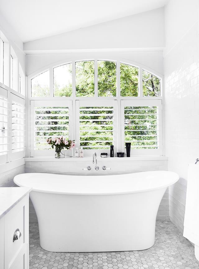 """Drawing on advice from interior designer Justine Hugh-Jones, Eugenie Kelly installed a double-ended freestanding bath, positioned under an arched window, with white tiled walls and marble hexagonal floor tiles in her beautiful [Arts and Crafts-style home](https://www.homestolove.com.au/arts-and-crafts-style-family-home-22192