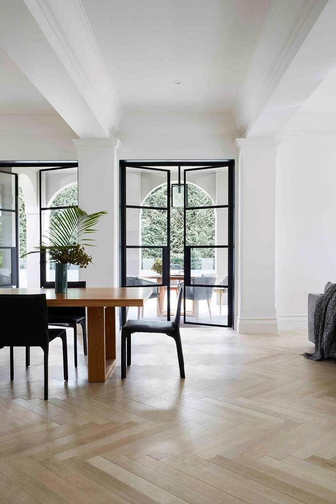 """The Zuster 'April' dining table in oak, with Living Edge black leather 'Saddle' chairs, establishes a smart but relaxed vibe in the dining space of this [Spanish-style home in bayside Melbourne](https://www.homestolove.com.au/modern-spanish-style-home-melbourne-21563
