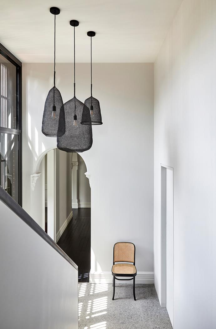 Looking from the new extension through to the existing hallway, the threshold is marked by the original archway and a change in flooring from granite to dark floorboards. 'Kute' pendant lights by Atmosphere D'Ailleurs from Spence & Lyda. 'No.811 Hoffmann' chair from Thonet.
