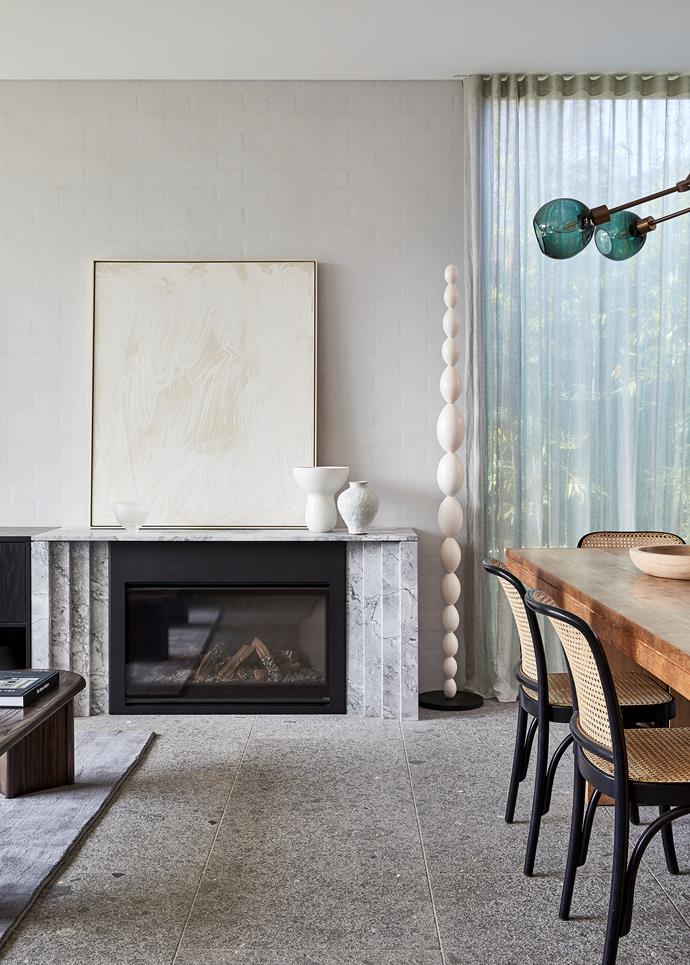 Fireplace surround in Super White honed stone from Gitani Stone. Aluminium sheet artwork on mantelpiece by Skye Jamieson. Ceramic floor sculpture by Walter Auer from Graphis Gallery.