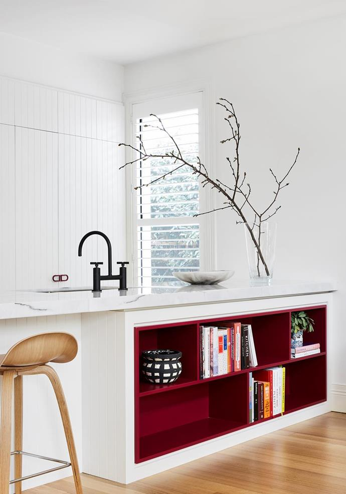 """Custom red door handles and a vibrant red open shelving section for cookbooks provides a subtle splash of colour and personality in the otherwise white kitchen of [this Melbourne home](https://www.homestolove.com.au/modern-joinery-ideas-21111