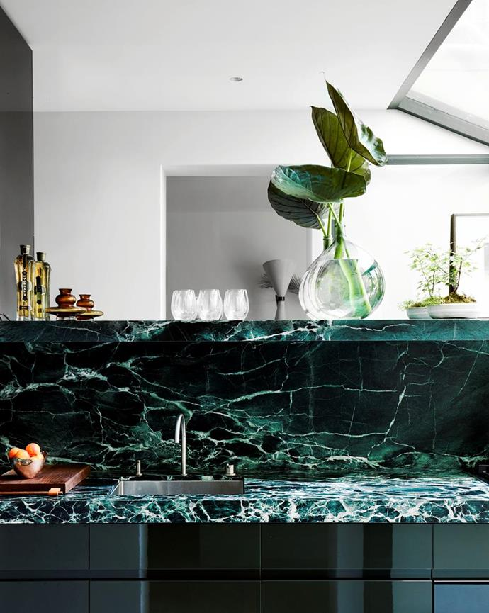 """Elegant emerald marble and dark green cabinetry adorns the luxurious kitchen in the inspirational [design studio of Sarah Davison](https://www.homestolove.com.au/sarah-davisons-design-studio-19231