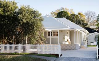 Grey and white cottage with tiled verandah and white picket fence