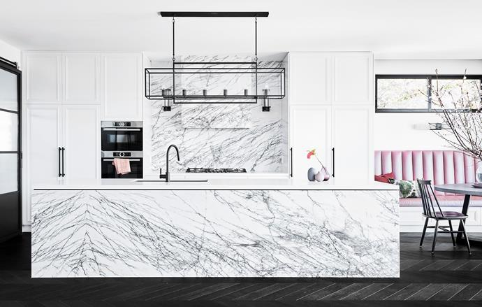 """**BEST KITCHEN - Sponsored by Blum**<br> **LAUREN MAHONEY OF STUDIO TRIO** <br> Both pattern and the colour pink hold great allure for the young family that owns this Sydney home. """"The homeowners adore New York marble so the whole kitchen was designed around it,"""" says interior designer Lauren. """"Because the island is so large – 3.1 metres – and the stone comes in 2.7-metre slabs the stonemasons had to match the pieces very carefully. They did a great job."""" The pink bench seating has been designed with family-friendliness in mind. """"The kids can do their homework at the table while their parents make dinner, and when it's time to eat they can lift the seat, pop their work in there and charge their iPads using the built-in USB ports while they're at it.""""  A striking box-lantern pendant from Visual Comfort allows a view through to the marble-clad rangehood and ties the kitchen in neatly with the steel-framed door to the left and window to the right."""