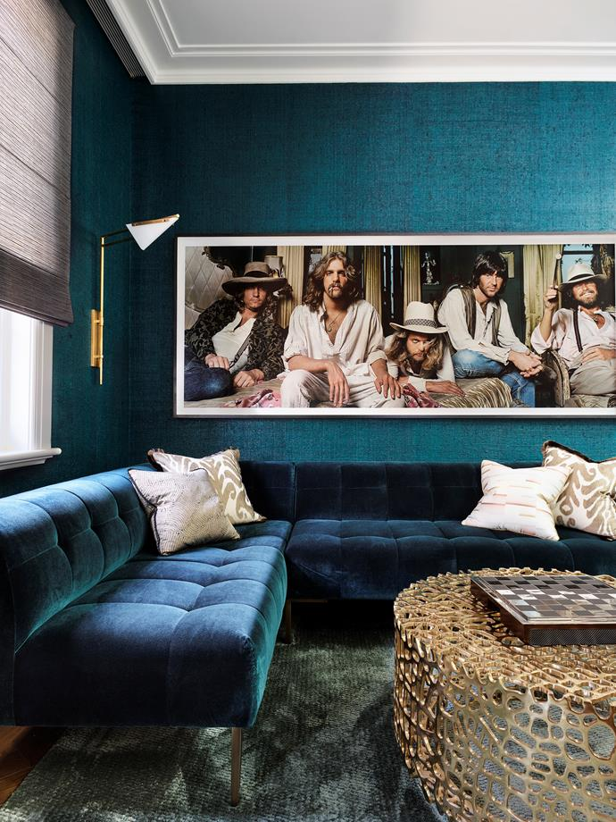"""**BEST USE OF ART - Sponsored by Lumas**<br> **THOMAS HAMEL OF THOMAS HAMEL & ASSOCIATES**<br> A life-size print of a 1970s photograph of rock band The Eagles is positioned for maximum impact in the bar/living area of this Sydney home. The placement of the Norman Seeff portrait – low on the wall, just above the velvet L-shape sofa – makes it feel like the five band members are languidly lounging in the room. Interior deesigner Thomas converted an under-utilised formal dining room to create this area, which is designed to operate as a coffee lounge during the day, bar by night. """"The teal wallpaper creates a sensational background for the amazing photograph,"""" says Thomas. """"I smile every time I see the gold lame bedcover in the foreground of the image."""" The owners love the 1970s Los Angeles vibe of this space: """"It has become the entertaining focal point of our home."""""""