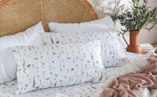 Floral bedding on a bed with a rattan headboard