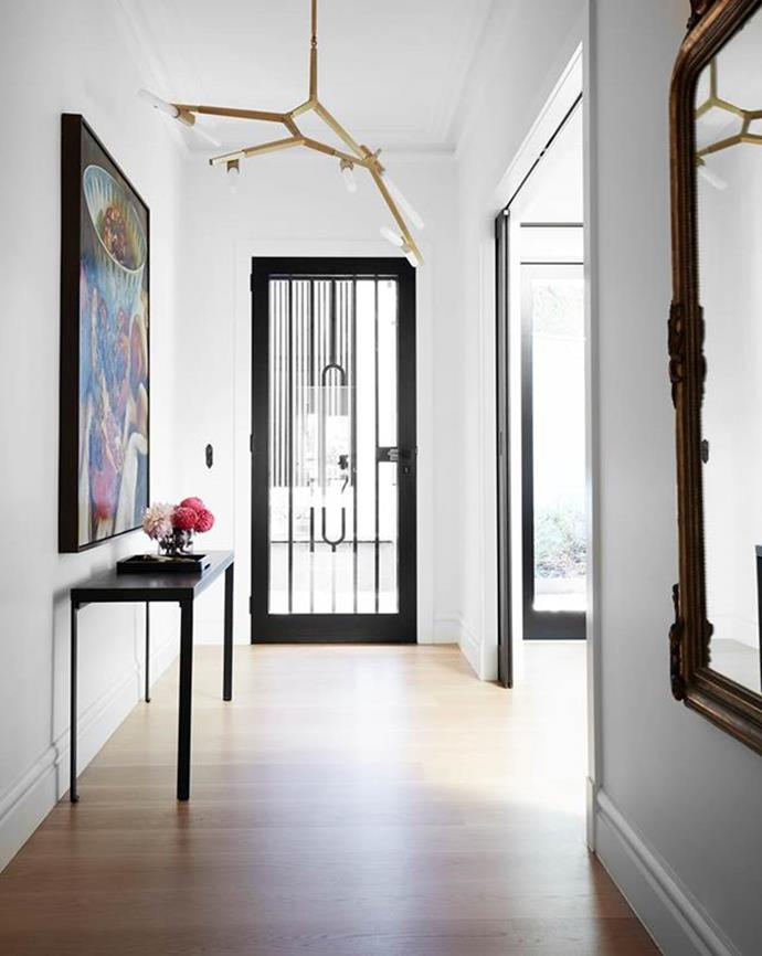 "The entry hallway in this [modern family home](https://www.homestolove.com.au/modern-family-home-with-japanese-influence-22163|target=""_blank"") was enlarged to accommodate a striking Dean Home artwork. American white oak boards from Floormania flow right through the ground floor."