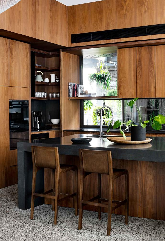 """**Down to earth** Deep timber tones form a warm backdrop to the kitchen in this [strikingly modern home](https://www.homestolove.com.au/modern-house-booker-bay-20437
