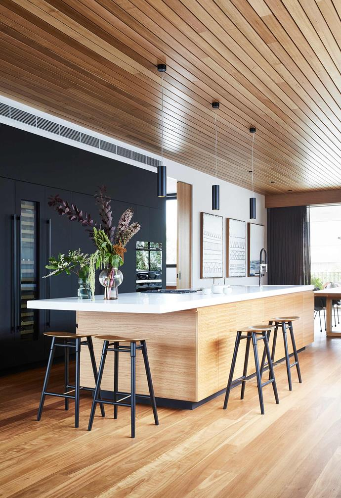"""**Light and dark** Dark kitchen cabinetry provides a moody backdrop to the timber-heavy kitchen in this [coastal home in Torquay that was built for entertaining](https://www.homestolove.com.au/contemporary-family-house-torquay-22236