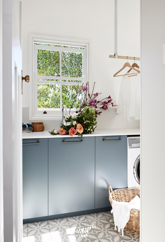 "Customised duck blue cabinetry doors in Laminex Winter Sky spruce up the light-filled laundry in this [elegant heritage Sydney home](https://www.homestolove.com.au/restored-heritage-home-sydney-21929|target=""_blank"") restored to its former glory."