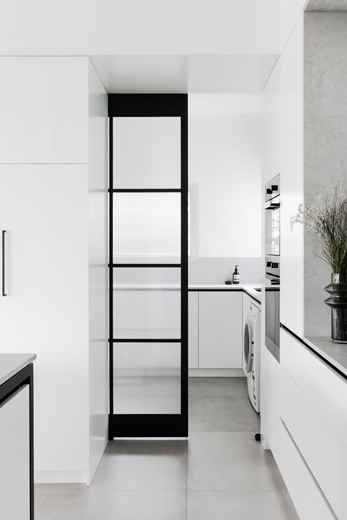 "Additional bench space in the laundry comes in handy when the family entertain in this [modern-minimal kitchen renovation](https://www.homestolove.com.au/minimalist-kitchen-design-21310|target=""_blank""), while a custom sliding door by Envisage Steel Creations can be pulled shut to close off the room when not in use."