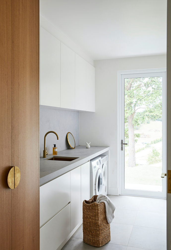 """With three young boys in this household the laundry in this [new-build in the Byron Bay hinterland](https://www.homestolove.com.au/new-build-byron-bay-hinterland-22186 target=""""_blank"""") gets a good workout, and is equipped with a functional layout and lots of bench space. The Caesarstone concrete and Lo & Co door handles continue here, with a brushed brass sink and tapware for added impact. A mirror from Marr-kett, a ceramic object from Nikau and Dior hand soap adorn the laundry benchtop."""