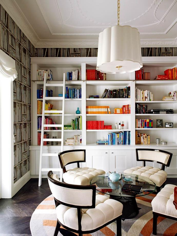 Ceiling-height book shelves run the length of the wall were custom-made for this apartment, while Cole & Son Fornasetti wallpaper creates a suitable backdrop for this Greg Natale designed home library.