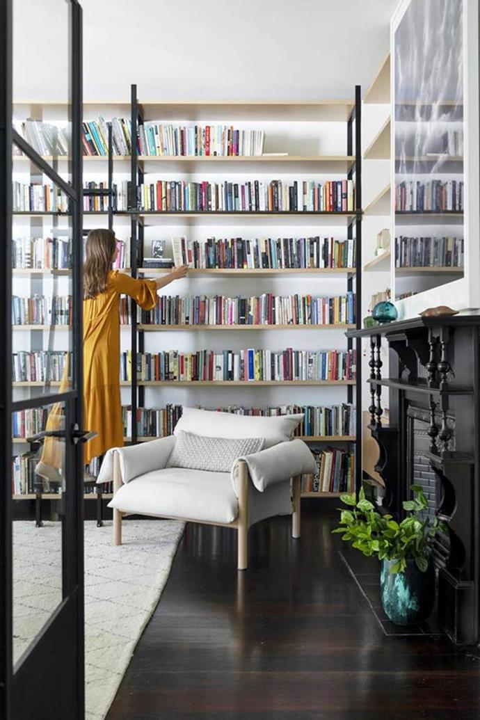 """""""My lifelong ambition was having floor-to-ceiling bookshelves with a sliding ladder, so it's nice to have achieved this!"""" says owner Alice Nelson. The ladder was made by Israeli metal artist Daniel Kasher and has lines from one of Alice's favourite Rilke poems engraved into the treads. 'Wilfred' chair from Jardan."""