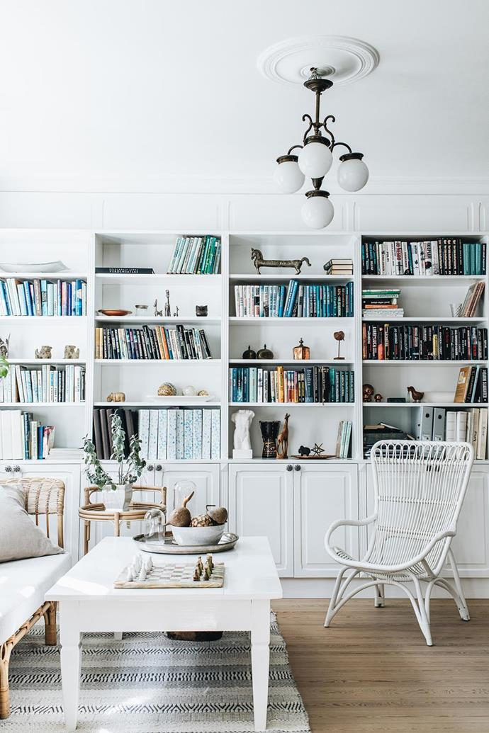 """The living room cabinet displays objects from travels alongside books to create an eclectic collection in an [old-fashioned home with classic Danish-style interiors](https://www.homestolove.com.au/danish-interior-design-21159
