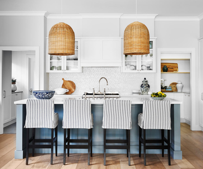 With a laundry on one side and a butler's pantry on the other, the kitchen is practical and pleasing to the eye. Custom slip covers in Fabricut 'Cosada Stripe' in Indigo by The Classic Outfitter for the stools are a classic touch.