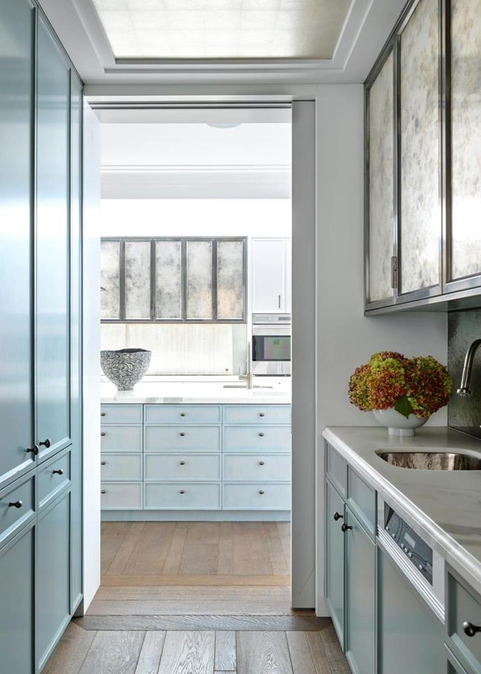 Looking through the butler's pantry to the kitchen with overhead cupboards finished in bespoke antique glass from Glass Artistry. Calacatta marble from Granite & Marble Works. Hansgrohe sink mixer from Candana. Vase from Ruth Levine. Flowers from Mandalay Flowers.