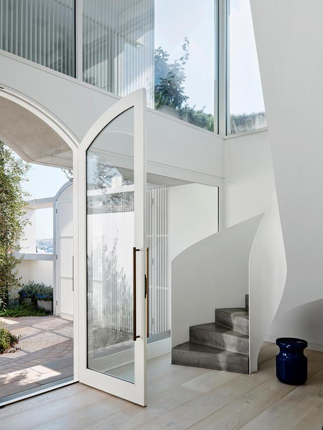 """Accessed via a sunlit courtyard dappled with shade from a mature olive tree, this breezy, [light-filled foyer](https://www.homestolove.com.au/ultra-modern-coastal-home-bondi-21968 target=""""_blank"""") creates a wonderful sense of arrival with its sweeping staircase gesturing visitors towards the upper floor."""