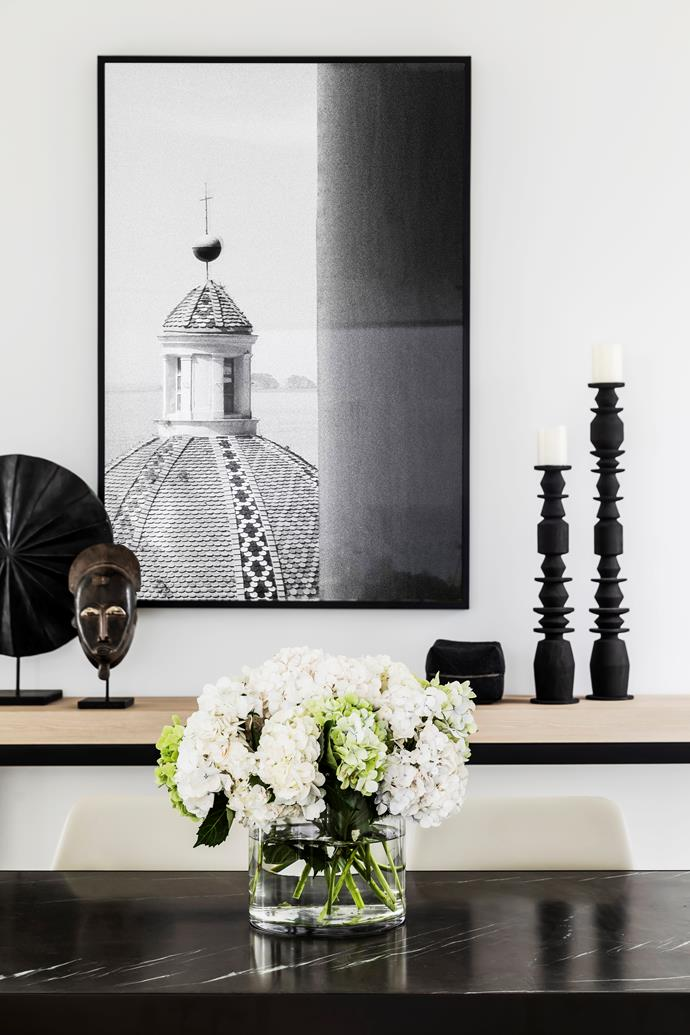 """In the dining room, a custom-designed table with a Pietra Grey marble top is teamed with Molteni&C 'Chelsea' chairs. The monochromatic scheme continues with candleholders and statues from Orient House and a photograph from a trip to Positano. """"It is taken from our favourite hotel, Le Sirenuse,"""" says Jack Freeman, who lives in this Mosman residence with his parents and sister."""
