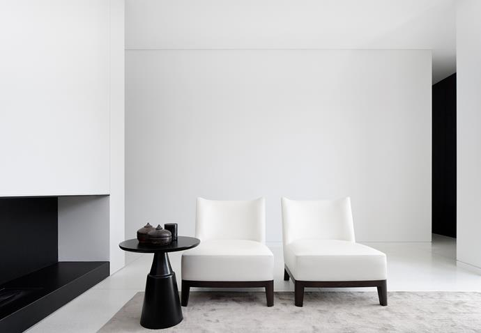 A black-granite fireplace creates depth in this sitting room. The armchairs are Christian Liaigre, the side table is by Holly Hunt and the African bowls are from recent travels.