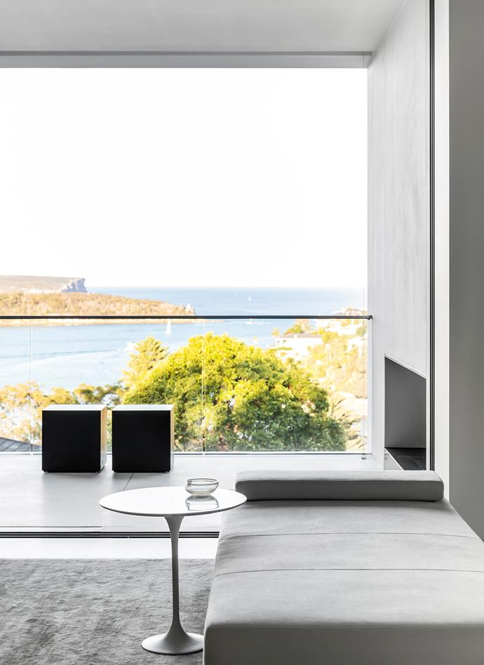 This balcony features a fireplace with a black granite hearth and insect screens that can be lowered over the balustrades, allowing for year-round comfort. Jack designed the cubes as well as the daybed in Loro Piana fabric in the adjoining living room. The table is an Eero Saarinen 'Tulip' and the art silk rug is from Tappeti.