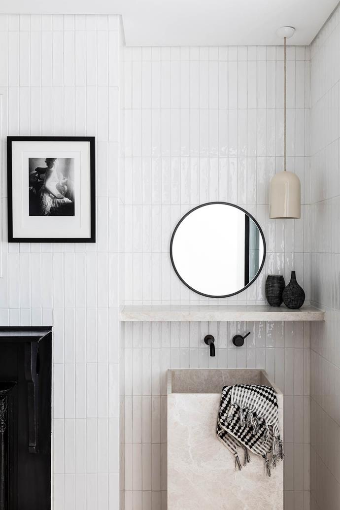 "In this [renovated terrace home](https://www.homestolove.com.au/modern-terrace-house-design-20335|target=""_blank"") a White Emperador marble basin and shelf were custom-made to be the heroes of the powder room. White subway tiles laid vertically on te walls helps to accentuate a sense of space, while a ceramic pendant light adds task lighting."
