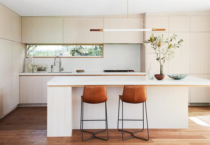 Meditation Fails artwork by Vanessa Stockard sits on the kitchen bench. A 'Sid' pendant light from Jardan is suspended above the kitchen island bench and 'Slope' leather bar stools from West Elm.