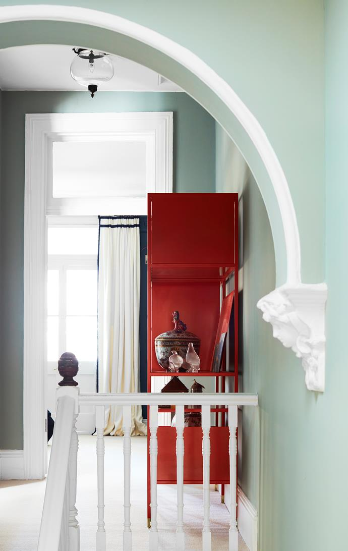 A red shelving unit designed by Chris Connell displaying collected curios pops against the walls.
