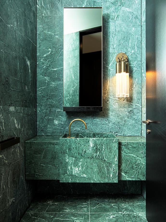 This powder room is realised in Ocean Green marble from Parthenon Marble. Flack Studio designed the custom basin, its chiseled form adding dimension to the immersive scheme.