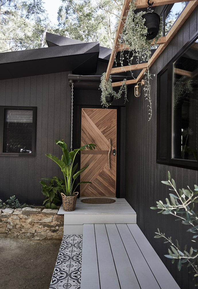 """The bold entrance to owner-builder Saul's new studio blends modern design with rustic materials, setting the tone for what lies beyond. An architectural butterfly shaped roofline crowns the exterior enveloped in James Hardie Linea Weatherboard, painted in Dulux Monument. A decked walkway, framed in patterned tiles from My Tile Co, leads to the bespoke front door Saul crafted from [timber flooring](https://www.homestolove.com.au/timber-versus-laminate-flooring-2680